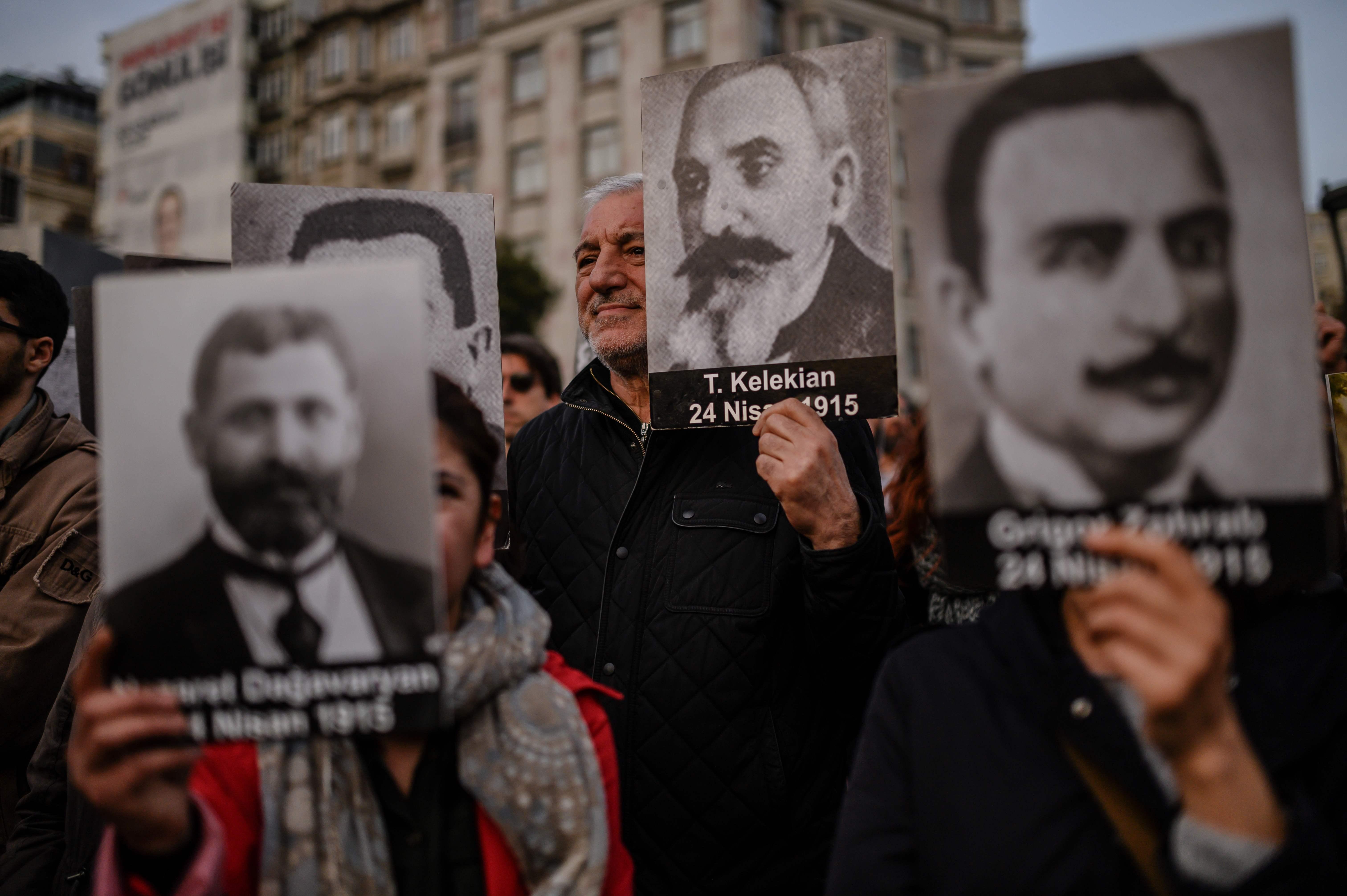أرمنيون يحملون صور ذويهم المفكرين ضحايا المذبحة خلال مسيرة فى إسطنبول (أ.ف.ب)
