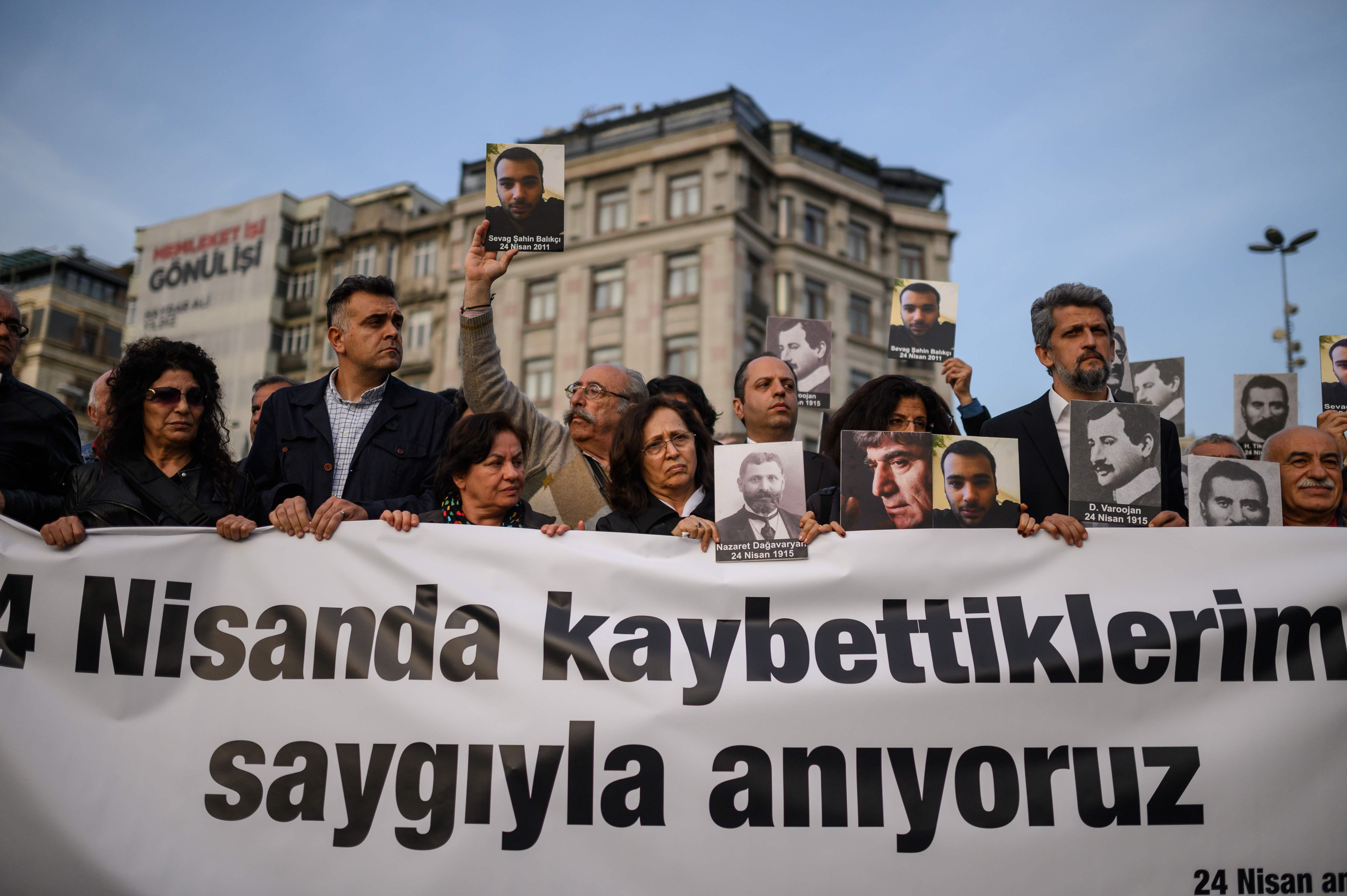 أرمنيون يرفعون صوراً لضحايا المذبحة خلال مسيرة فى إسطنبول (أ.ف.ب)